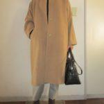 ベージュノーカラーコートと黒のタートルネックセーター